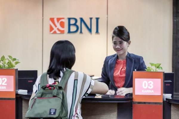 Staf Bank BNI (kanan) melayani nasabah di Jakarta pada Selasa (6/11/2018).  - GB / Felix Jodi Kinarwan