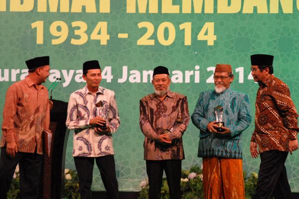 Dirut BNI Gatot M. Suwondo (kanan) memberikan penghargaan Nahnu Ansorulloh kepada 3 pimpinan pesantren di bawah naungan Nahdlatul Ulama (NU) yang sukses dalam mengembangkan perekonomian komunitas pada peringatan Hari Lahir ke-80 Gerakan Pemuda Ansor (GP Ansor) di Surabaya, Jatim, Sabtu (4/1/2014) malam. Gerakan Pemuda Ansor memilih 3 kiai tersebut sebagai inspirator pemberdayaan masyarakat.  - antara