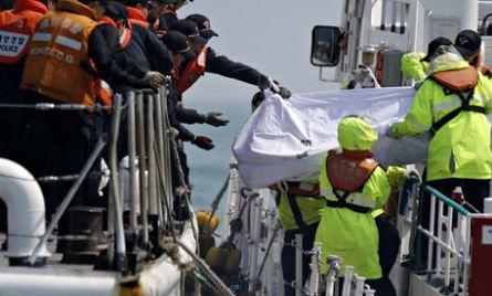 Pasukan penjaga pantai Korea Selatan memindahkan tubuh korban yang terbungkus ke dalam kapal saat mereka menemukan korban dari feri Sewol yang tenggelam. - Reuters/Issei Kato
