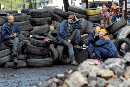 Ilustrasi-Petugas kebersihan balai kota beristirahat di tumpukan barikade ban di pusat kota Kiev (23/4/2014). - Reuters/Valentyn Ogirenko