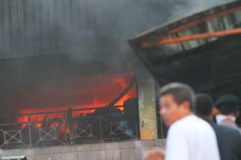 Petugas yang menggunakan pengeras suara, mengimbau para pedagang untuk tidak memaksa masuk ke kawasan toko yang terbakar. - antara