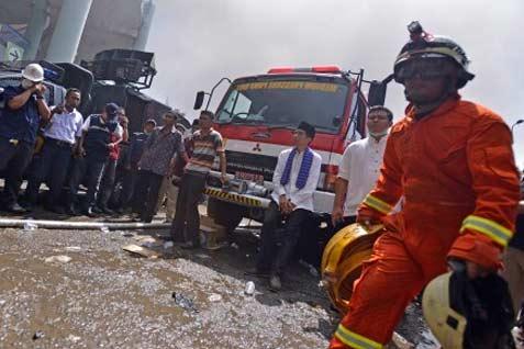 Gubernur DKI Jakarta Joko Widodo (ketiga kanan) duduk di mobil pemadam saat meninjau gedung Pasar Senen yang terbakar, Jakarta Pusat, Jumat (25/4). Puluhan unit pemadam kebakaran dikerahkan untuk memadamkan api yang diperkirakan mulai melanda gedung lama pasar itu sekitar pukul 04.00.  - antara