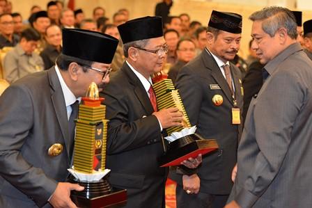 Presiden Susilo Bambang Yudhoyono (kanan) saat menyerahkan tanda kehormatan Samkaryanugraha Parasamya Purnakarya Nugraha kepada Gubernur Jatim Sukarwo (kiri), Wagub Jateng Heru Sudjatmoko (kedua kiri) dan Gubernur Sulsel Syahrul Yasin Limpo (kedua kanan) pada acara peringatan Hari Otonomi Daerah ke-18 Tahun 2014 di Istana Negara, Jakarta, Jumat (25/4/2014). - Antara