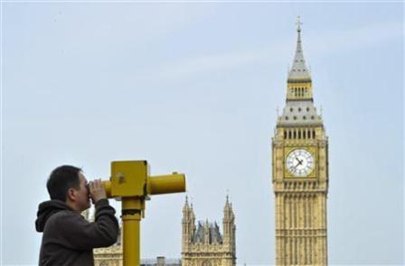 Ilustras-Seorang pria melihat melalui teleskop di seberang Big Ben dan Gedung Parlemen Inggris di pusat kota London (6/5/2011). - Reuters/Toby Melville