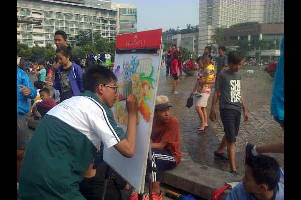 Seorang pelukis tengah melukis dengan objek di Bundaran HI Jakarta. (Rahmayulis Saleh)