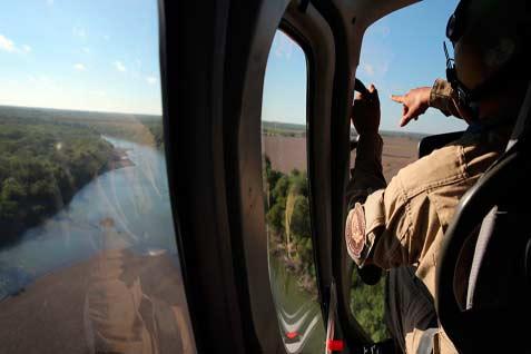 Seorang awak helikopter dari Kantor Perairan dan Kelautan AS terbang di atas Rio Grande dekat Rio Grande City, Texas, pada 10 September, 2014. Helikopter dari badan ini, bagian dari US Customs dan Perlindungan Perbatasan, berpatroli perbatasan AS-Meksiko sepanjang siang dan malam.  - Getty Images/Bloomberg