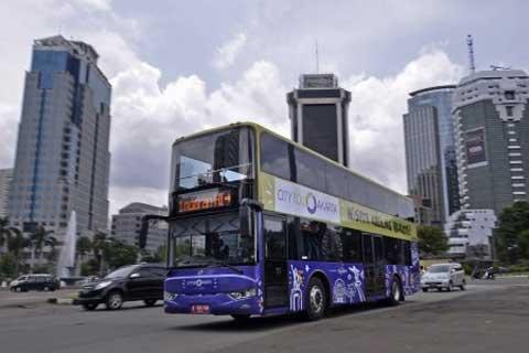 Bus Wisata Jakarta melintas di Bundaran Bank Indonesia, Jakarta Pusat, Senin (24 - 2).