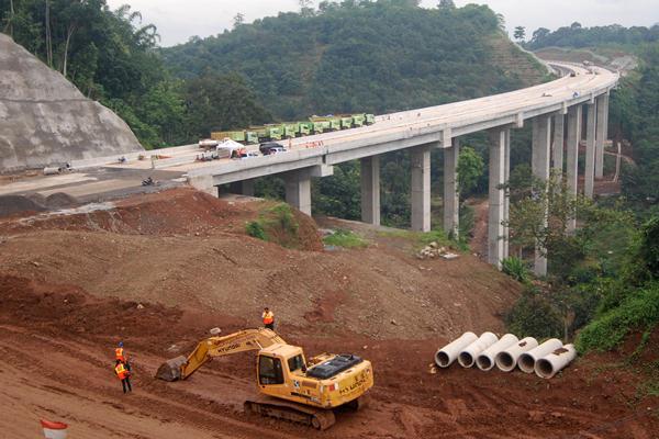 Sejumlah pekerja menggarap pembangunan Jembatan Tuntang di ruas Tol Bawen-Salatiga di Bawen, Kabupaten Semarang, Jawa Tengah, Kamis (26/1). Menurut PT Trans Marga Jateng (TMJ) selaku operator, pembangunan tol sepanjang 17,57 kilometer tersebut baru terealisasi 81,623 persen dari target 91,6 persen karena terkendala intensitas hujan tinggi. ANTARA FOTO - Aditya Pradana Putra