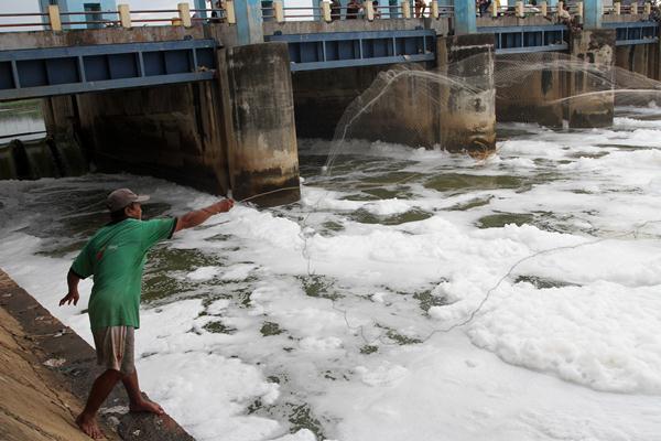 Warga menjala ikan di pintu air yang dipenuhi busa, di hulu Kanal Banjir Timur, Jakarta Utara, Kamis (9/2).  - Antara