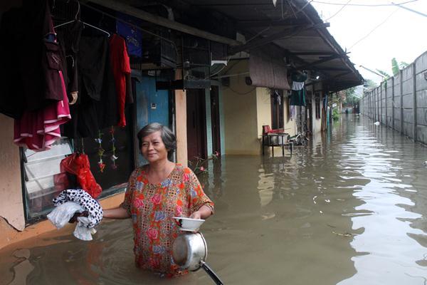 Warga melintasi banjir yang merendam kawasan permukiman Kampung Buaran, Harapan Mulya, Bekasi, Jawa Barat, Minggu (19/2). Sebanyak 95 rumah di daerah tersebut terendam banjir akibat intensitas curah hujan tinggi yang membuat pintu air di kawasan tersebut meluap. ANTARA FOTO - Risky Andrianto