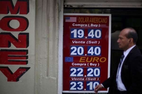 Seorang pria tengah melintasi papan yang menunjukkan nilai tukar peso terhadap dolar AS. - .Reuters