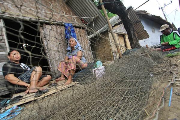 Nelayan (kanan) memperbaiki jaring di halaman rumahnya di desa Singaraja, Indramayu, Jawa Barat, Kamis (23/2). - Antara/Dedhez Anggara
