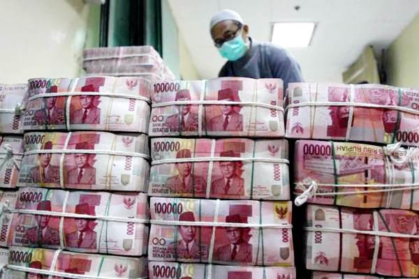 Petugas menata tumpukan uang rupiah. - JIBI/Abdullah Azzam