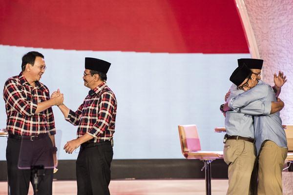 Calon Gubernur dan Wakil Gubernur DKI Jakarta Basuki Tjahaja Purnama (kiri) berjabat tangan dengan Djarot Saiful Hidayat (kedua kiri), sementara calon Gubernur DKI Jakarta Anies Baswedan (kedua kanan) berpelukan dengan wakilnya Sandiaga Uno, seusai Debat Publik Pilkada DKI Jakarta putaran kedua di Hotel Bidakara, Jakarta, Rabu (12/4). - Antara/M Agung Rajasa