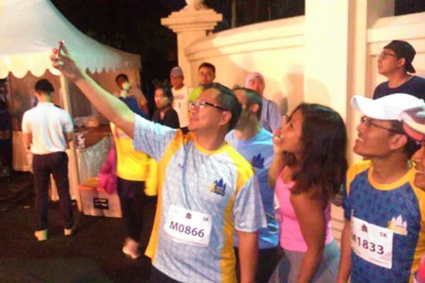 Direktur Utama Bank Mandiri Kartika Wirjoatmodjo melakukan foto bersama sejumlah peserta Mandiri Jogja Marathon 2017, Minggu (23/4/2017). - Bisnis/Stefanus Arief Setiaji