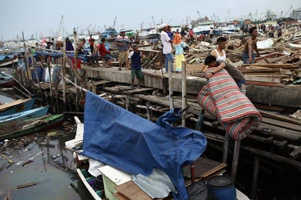 Ilustrasi: Warga mengangkut sisa barang di salah satu bangunan yang telah dibongkar di kawasan Kampung Luar Batang, Pasar Ikan, Jakarta Utara, Selasa (12/4/2016). - Antara