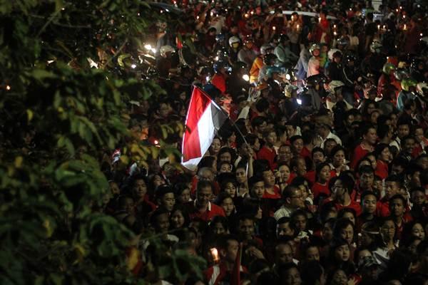 Ribuan warga menggelar doa saat melakukan aksi Seribu Lilin untuk NKRI di Surabaya, Jawa Timur, Jumat (12 - 5). Aksi tersebut merupakan bentuk dukungan terhadap Basuki Tjahja Purnama (Ahok) sekaligus seruan untuk mempertahankan Pancasila dan NKRI. ANTARA FOTO
