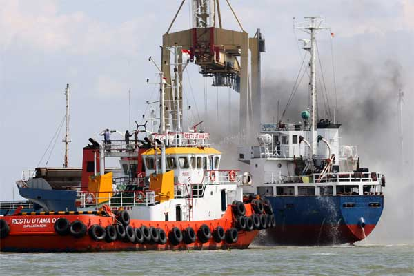 Petugas melakukan pembasahan pada Kapal Motor (KM) Asia Prima I yang terbakar di Selat Madura, Surabaya, Jawa Timur, Jumat (5/5). - Antara/Didik Suhartono