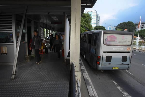 Calon penumpang bus Transjakarta berjalan di halte Transjakarta di Jakarta, Senin (11/1). - Antara