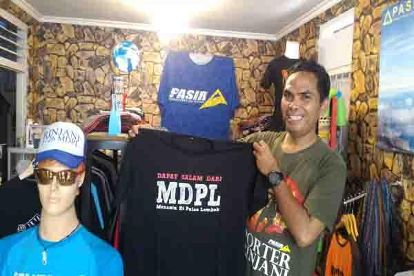 Sukarno bersama dengan pernak-pernik khas Rinjani di tokonya - Bisnis.com