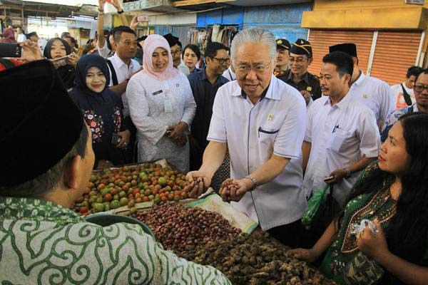 Menteri Perdagangan Enggartiasto Lukita (tengah) berbincang dengan pedagang daging saat kunjungan di Pasar Blambangan, Banyuwangi, Jawa Timur, Selasa (20/6). - Antara/Budi Candra Setya