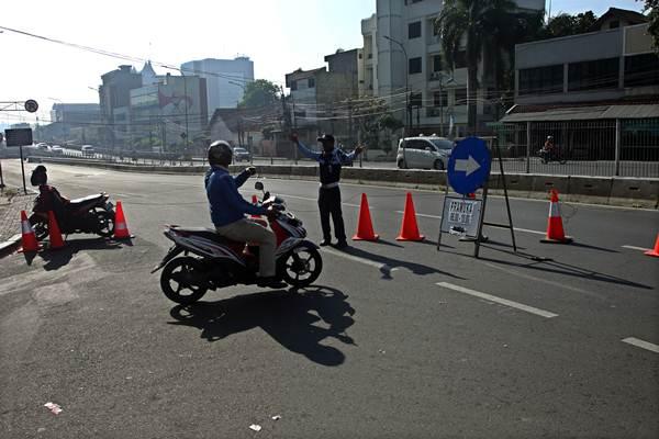 Petugas mengarahkan kendaraan untuk melaju ke arah jalan Pramuka saat pengalihan arus lalu lintas di jalan Pramuka, Jakarta, Rabu (21/6). Untuk mengantisipasi kemacetan akibat pembangunan