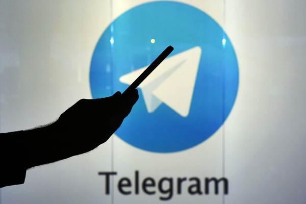 Siluet tangan seorang pria memegang ponsel di depan logo Telegram. - Bloomberg
