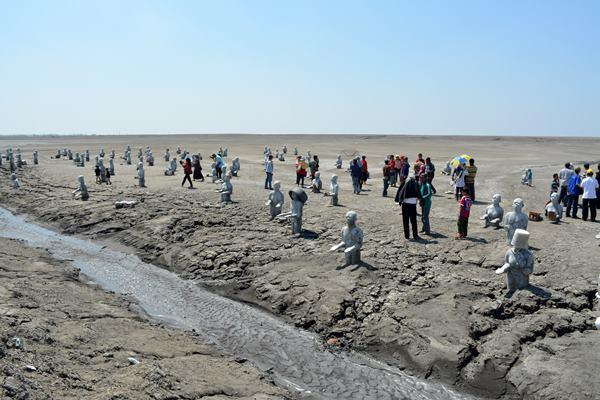 Sejumlah wisatawan melihat seratus patung sisa peringatan 8 tahun semburan lumpur lapindo yang ada area tanggul penahan lumpur Porong, Sidoarjo, Jawa Timur, Minggu (10/5). - Antara