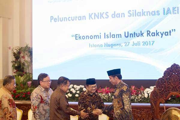 Presiden Joko Widodo (kanan) berjabat tangan dengan Presiden Ketiga RI BJ Habibie, disaksikan Wakil Presiden Jusuf Kalla (tengah), Menteri PPN/Kepala Bappenas Bambang Brodjonegoro (kedua kiri), dan Menko Perekonomian Darmin Nasution saat peluncuran Komite Nasional Keuangan Syariah (KNKS) dan peresmian pembukaan Silaturahmi Kerja Nasional (Silaknas) Ikatan Ahli Ekonomi Islam Indonesia (IAEI) di Istana Negara, Jakarta, Kamis (27/7). - ANTARA/Rosa Panggabean