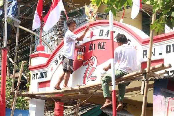 Warga mengecat gapura untuk menyambut HUT Kemerdekaan RI.  -