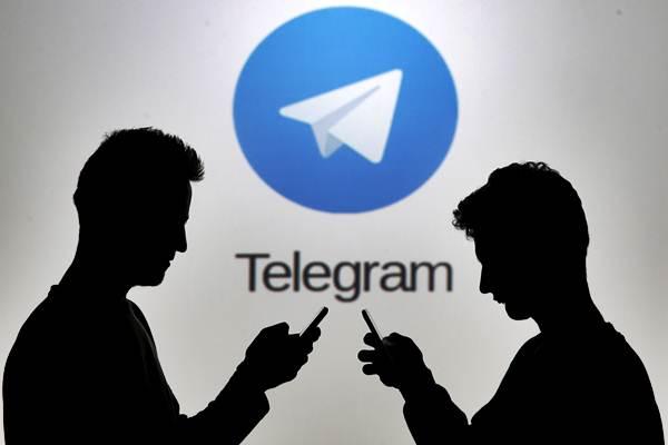 Siluet pengguna ponsel di depan logo Telegram. - Reuters