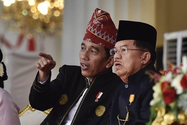 Presiden Joko Widodo (kiri) berbincang dengan Wakil Presiden Jusuf Kalla saat upacara penurunan bendera Merah Putih dalam rangka HUT ke-72 RI di Istana Merdeka, Jakarta, Kamis (17/8). - ANTARA/Puspa Perwitasari