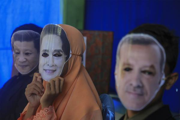 Siswa SMP Muhammadiyah 7 Solo mengenakan topeng bergambar Pemimpin Myanmar Aung San Suu Kyi (tengah) Presiden Turki, Recep Tayyip Erdogan (kanan) dan Presiden Cina, Xi Jinping (kiri) saat mencalonkan diri dalam pemilihan ketua Organisasi Siswa Intra Sekolah (OSIS) di sekolah setempat, Solo, Jawa Tengah, Jumat (15 - 9). Dalam ajang pemilihan ketua osis yang juga digunakan sebagai aksi solidaritas bertajuk Save Rohingya tersebut mereka mereka meminta pimpinan/ pimpinan negara di seluruh dunia turut menyelesaika