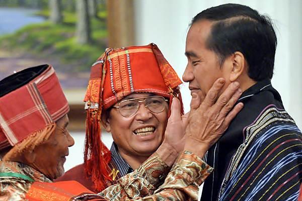 Presiden Joko Widodo (kanan) menerima sematan Kain Ulos khas Batak dari perwakilan Masyarakat Hukum Adat (MHA) Pandumaan Sipituhuta Kabupaten Humbang Hasundutan, Sumut usai acara Pencanangan Pengakuan Hutan Adat Tahun 2016 di Istana Negara, Jakarta, Jumat (30/12/2016). - Antar/Widodo S. Jusuf