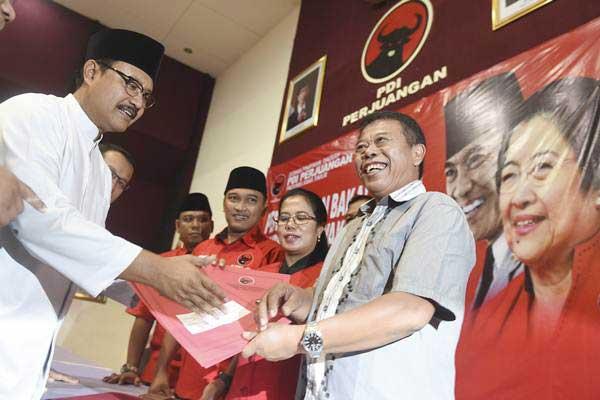 Ketua DPD PDIP Jatim Kusnadi (kanan) menerima pengembalian formulir bakal calon Gubernur Jatim dari Wakil Gubernur Jawa Timur Saifullah Yusuf (kiri) di kantor DPD PDIP Jatim, Surabaya, Jawa Timur, Senin (3 - 7).ANTARA/Zabur Karuru