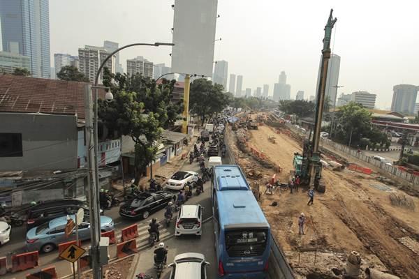 Kendaraan melintas di samping pembangunan terowongan (underpass) Mampang Prapatan-Kuningan di kawasan Mampang, Jakarta, Kamis (13/7). Pembangunan underpass yang menelan biaya Rp200 milia dan kan dibangun sepanjang kurang lebih 800 meter dengan lebar 20 meter atau empat lajur jalan sehingga diharapkan dapat memperlancar arus kendaraan dari arah Mampang menuju Kuningan maupun sebaliknya. ANTARA FOTO - Muhammad Adimaja