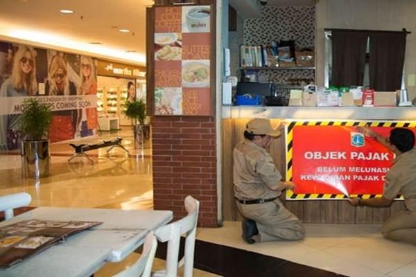 Petugas Pajak Jakarta Selatan memasang stiker pemberitahuan utang pajak di sebuah kedai di Pondok Indah Mall 2, Jakarta. - Antara