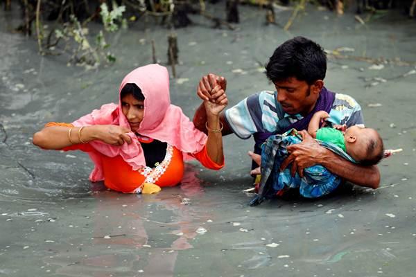 Pengungsi Rohingya membawa bayi mereka menerobos sungai setelah berhasil menyeberangi perbatasan di Teknaf, Bangladesh, Kamis (7/9). - REUTERS/Mohammad Ponir Hossain