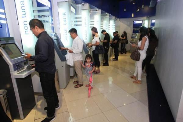 Nasabah melakukan transaksi perbankan melalui anjungan tunai mandiri di Jakarta, Minggu (4/6). - JIBI/Dedi Gunawan