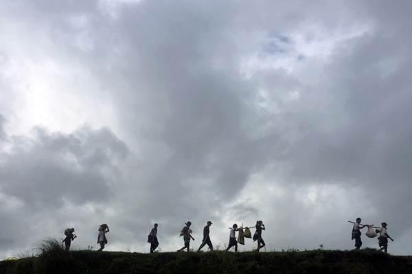 Warga yang terusir akibat kekerasan di wilayahnya berjalan melalui tepian sungai Mayu bersama bawaan mereka saat mengungsi ke wilayah lain di Buthidaung, kawasan utara negara bagian Rakhine, Myanmar - Reuters/Stringer