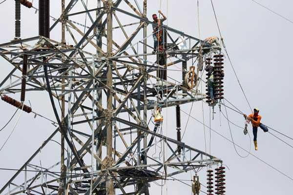 Teknisi melakukan penggantian kabel listrik Saluran Udara Tegangan Tinggi (SUTT) di Surabaya, Kamis (28/9). - ANTARA/Didik Suhartono