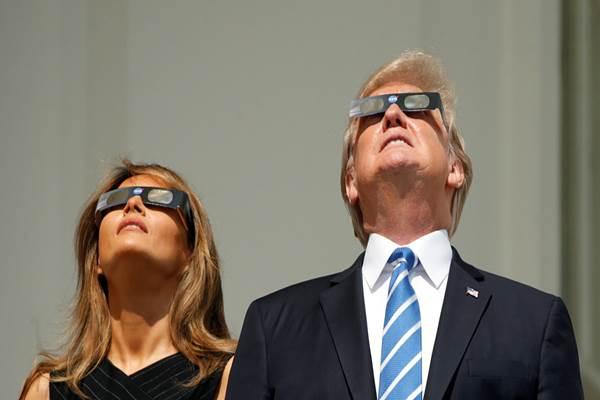 Presiden AS Donald Trump dan Ibu Negara AS Melania Trump saat menyaksikan gerhana matahari total, Senin (21/8/2017) waktu setempat. - Reuters