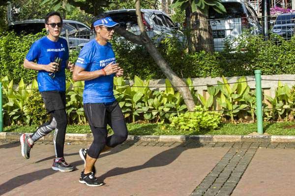 Wakil Gubernur DKI Jakarta Sandiaga Uno (kanan) berlari menuju Balai Kota, di Jakarta - ANTARA/Galih Pradipta