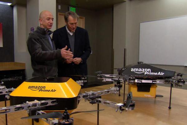 CEO Amazon Jeff Bezos (kiri) menjelaskan prototipe drone pengirim paket kepada Charlie Rose dari CBS. - CBS