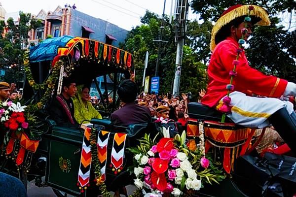 Presiden Joko Widodo dan Ibu Negara Iriana Joko Widodo di dalam iring-iringan Kirab Budaya Pesta Pernikahan Bobby-Kahiyang di Medan, Minggu 26 November 2017. - JIBI / Yoseph Pencawan