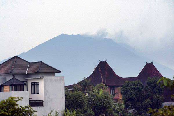 Asap kelabu menyembur dari puncak Gunung Agung, terpantau dari Kabupaten Gianyar, Bali, Selasa (21/11). - ANTARA/Nyoman Budhiana