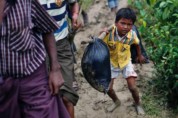 Anak pengungsi Rohingya memikul barang bawaannya, di Bangladesh, Selasa (19/9). - Reuters/Danish Siddiqui