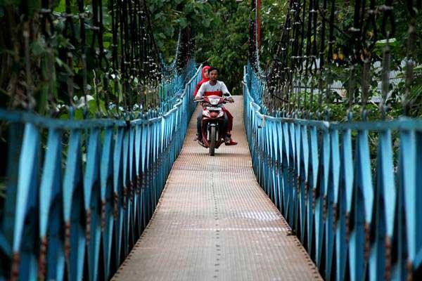 Ilustrasi-Pengendara sepeda motor melintas di jembatan gantung Desa Sangkurio, Mamuju, Sulawesi Barat, Rabu (4/10). - ANTARA/Akbar Tado