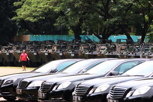 Seorang pria melintas di depan panser Anoa yang akan dipakai untuk mengamankan rombongan kedatangan Raja Salman di Parkir Timur Senayan, Jakarta, Selasa (28/2). Sebanyak 300 mobil mewah jenis Mercedes Benz tipe E, Mercedez Benz tipe S dan Alphard model terbaru serta panser Anoa disiapkan untuk melayani dan mengamankan para tamu delegasi Kerajaan Arab Saudi pada 1-3 Maret mendatang. ANTARA FOTO - Rivan Awal Lingga