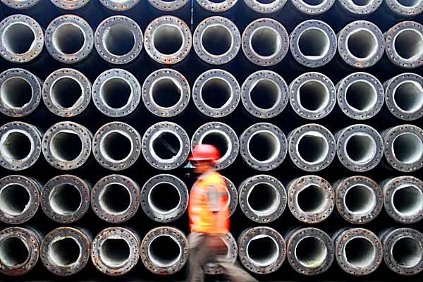 Pekerja melintas di dekat tumpukan beton di pabrik PT Wijaya Karya Beton Tbk. - JIBI/Nurul Hidayat